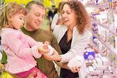 Familj med liten flicka köpa mjölk i snabbköp — Stockfoto