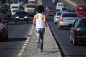 Tjejen kör på motorväg mitt i city, vy från baksidan — Stockfoto