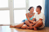 Enamoured man and woman sitting on floor near big window in cosy — Stock Photo