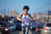 Dziewczyna biegnie na środku autostrady w mieście — Zdjęcie stockowe