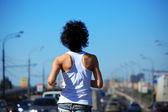 Flicka går på vägen bland bilar, bakifrån på bälte — Stockfoto