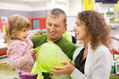 Family with girl buy cabbage in supermarket — Stockfoto