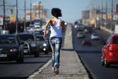 Girl runs on highway middle in city — Stock Photo