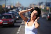 Flicka lyssnar musik i örat-telefoner på motorvägen mitten — Stockfoto