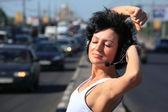 Garota no fone de ouvido situado no meio da estrada — Foto Stock