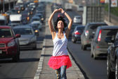Girl in pink skirt goes on highway middle — Stock Photo