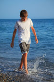 Teenager boy going on seacoast — Stock Photo