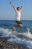 Jumping teenager boy on stone seacoast — Stock Photo