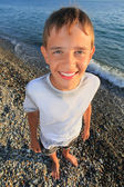 Smiling teenager boy standing on seacoast — Stock Photo