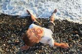 Sentado chico adolescente mirando hacia arriba en piedra de la costa, cuota de espaldas mojadas — Foto de Stock