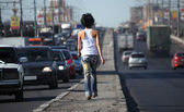 Girl goes on highway middle in city, view from back — Stock Photo