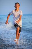 Kumsalda ıslak giysileri içinde çalışan genç çocuk — Stok fotoğraf