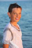 Garoto adolescente em roupas molhadas no litoral — Fotografia Stock