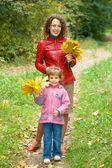 Klein meisje en jonge vrouw met esdoorn bladeren in handen in park — Stockfoto