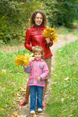Little girl and young woman with maple leaves in hands in park i — Stock Photo
