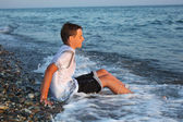 Sitting teenager boy in wet clothes on stone seacoast — ストック写真