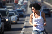 Girl runs on highway middle in city, view on belt — Stock Photo