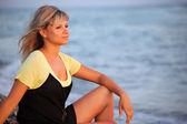 Sitting beautiful young woman on seacoast — Stock Photo