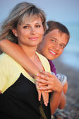 Smiling boy embraces young woman on beach in evening — Stock Photo