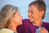 Smiling boy and young woman on beach in evening, Looking against — Stock Photo