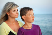 Boy and young woman on beach in evening, Looking afar — Stock Photo