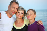 Happy family with smiling boy on beach in evening — Stock Photo