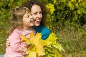 Joven mujer y niña reír con hojas en manos en el jardín — Foto de Stock