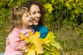 Young woman and little girl laugh with leaves in hands in garden — Stock Photo