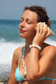 Beautiful woman has leant seashell bowl to an ear on seacoast — Stock Photo