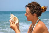 Beautiful woman considering seashell on seacoast — Stok fotoğraf