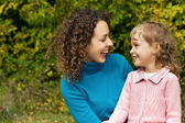 Young woman and little girl laugh in garden — Stock Photo
