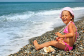 Pretty little girl with seashell and necklace on stone seacoast — Stock Photo