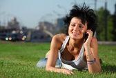 Jeune fille se trouve sur la pelouse au chemin en ville et parle par téléphone — Photo