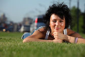 Girl lies on lawn at road in city — Stock Photo