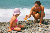 Young woman gives starfish to little girl on stony beach — Stock Photo