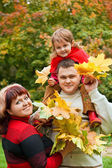 Married couple and little girl collect maple leafs In park in au — Stock Photo