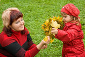 Woman and little girl collect maple leafs In park in autumn — Stock Photo