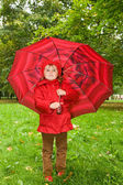 Little girl with umbrella in park — Stock Photo