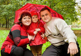 Matrimonio y niña con paraguas en el parque — Foto de Stock
