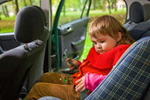 Little girl sit in car in park — Stock Photo