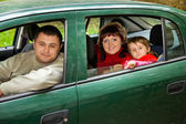 Married couple and little girl sit in car in park — Stock Photo