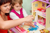 Little Girl and woman washes a doll in pool of toy house — Stock Photo