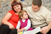 Married couple and little girl read book in a cosy room — Stock Photo