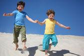 Dos chicos correr sobre arena — Foto de Stock