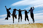 Group of friends jumps on sand, rear view — Stock Photo