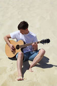 Guy plays guitar sitting on sand — Stock Photo