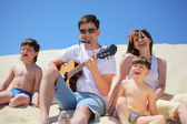 Guy in sunglasses plays guitar and lip accordion with children — Stock Photo