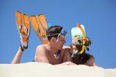 Unga par i fenor och undervattens masker ligger på sand — Stockfoto