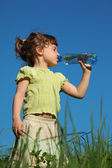Girl standing in grass drinks water from plastic bottle — Stock Photo