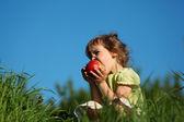 Chica come manzana roja en pasto contra el cielo azul — Foto de Stock